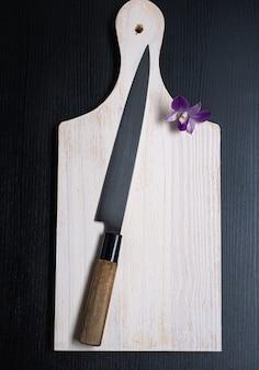 Sushi-messer auf einem weißen holzbrett und einer orchidee daneben