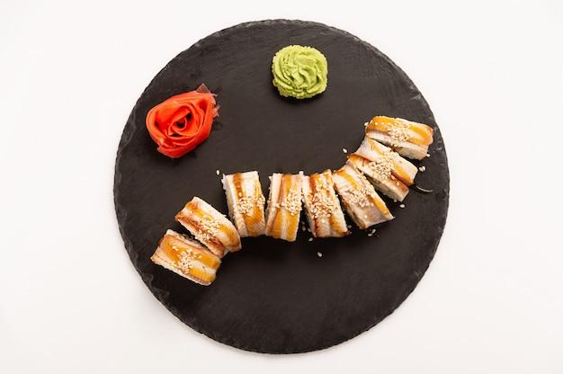 Sushi mit aalfisch auf einem schwarzen runden stein. draufsicht.