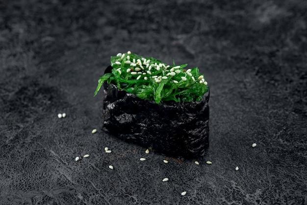 Sushi mit algen und sesam auf steinhintergrund. japanisches gericht chuka sushi, nahaufnahme