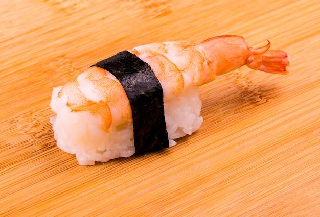 Sushi mit garnelen auf einem hölzernen stand.