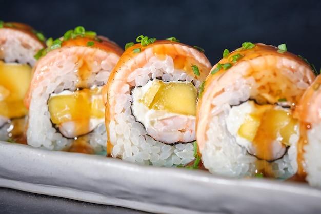 Sushi mit geflammten lachsgarnelen mango-frischkäse-schnittlauch und teriyakisauce