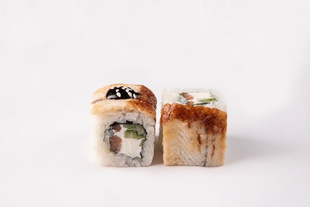 Sushi mit geräuchertem aal, philadelphia-käse, gurke, thunfisch und sesam mit unagi-sauce auf einem weißen raum