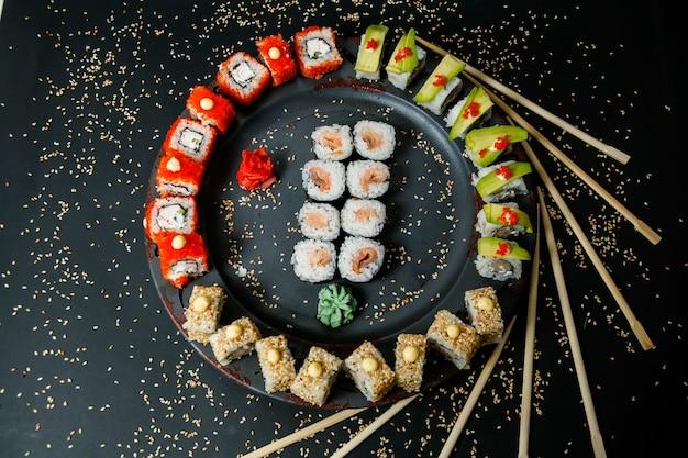 Sushi mit gurken-, ingwer-, wasabi- und sesamkörnern