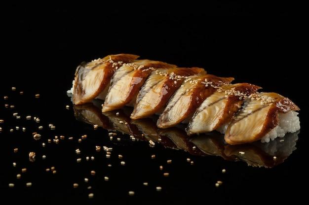 Sushi mit reis und sesam auf dunklem hintergrund mit reflexion