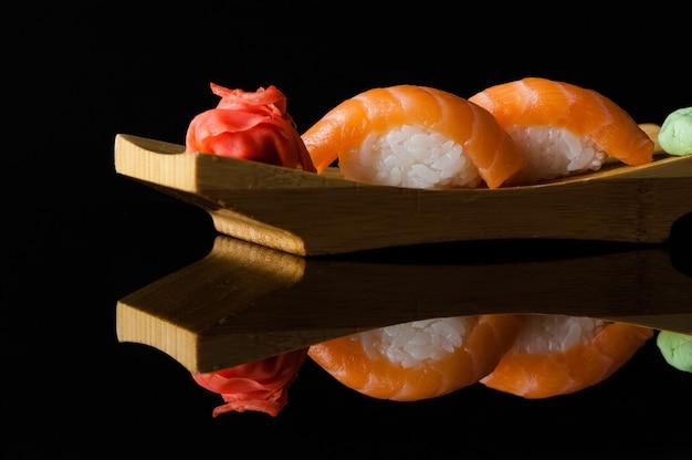Sushi mit reis und wasabi auf einem holzbrett auf dunklem hintergrund mit reflexion