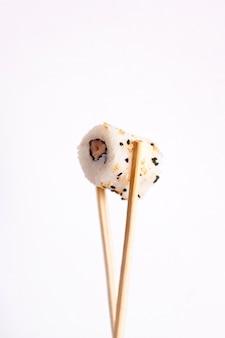 Sushi mit stäbchen essen. japanisches essen der sushi-rolle im restaurant lokalisiert auf weißem hintergrund.