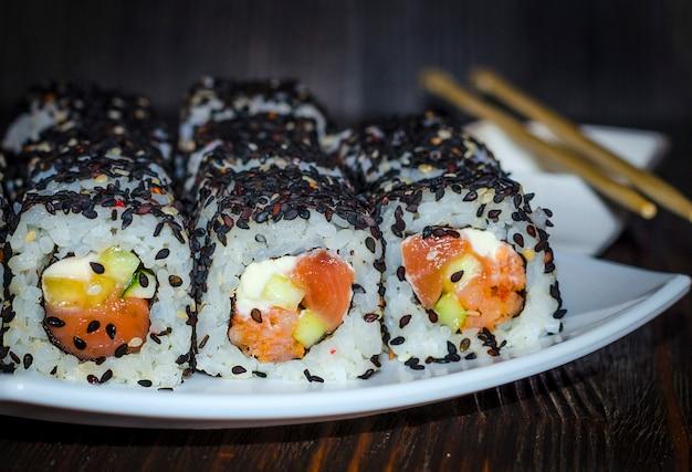 Sushi mit thunfisch in schwarzem sesam auf dunklem hintergrund