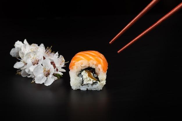 Sushi mit zweig weißer blumen auf dem schwarzen tisch.