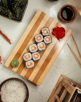 Sushi nori mit sojasoße auf einer hölzernen servierplatte.