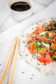 Sushi-pizza mit lachs, hayashi wakame, daikon, eingelegtem ingwer, rotem kaviar.