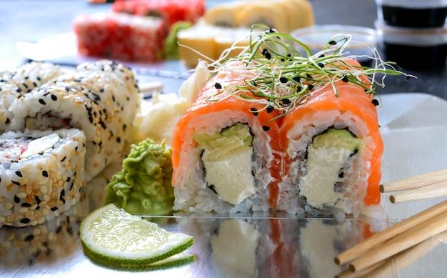 Sushi restaurant menü. set sushi-rollen, sauce, wasabi und hand mit stäbchen auf dunklem tisch. verschiedene arten von sushi. japanisches essen