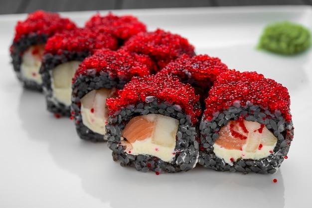 Sushi roll aus frischem lachs, avocado und frischkäse mit schwarzem reis