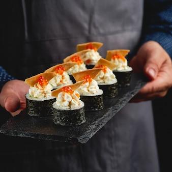 Sushi roll maki futo japanisches essen mit reis für sushi, nori, avocado, lachsfilet, käse, nachos, roter kaviar auf schwarzem stein teller.