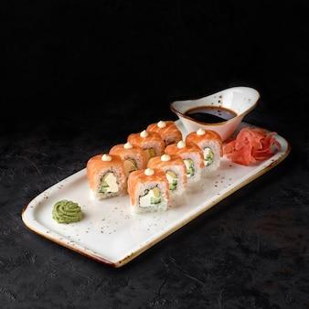 Sushi roll-philadelphia mit lachs, räucheraal, avocado, frischkäse auf schwarzem hintergrund. sushi-menü. japanisches essen