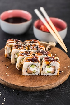 Sushi-rolle mit aal, lachs, gurke und frischkäse auf einer dunklen oberfläche