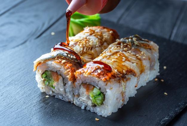 Sushi-rolle mit frischkäse und aal schließen. sushi auf dunklem steinplatte auf schwarzer holzwand mit kopienraum. japanisches essen. teriyaki-sauce auf sushi gießen