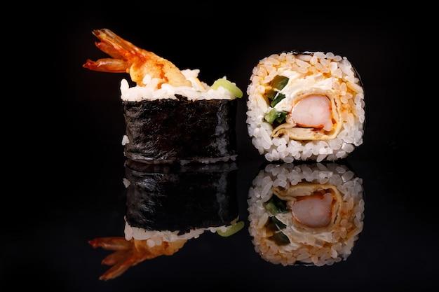 Sushi-rolle mit garnelen auf einer schwarzen oberfläche mit reflexion.