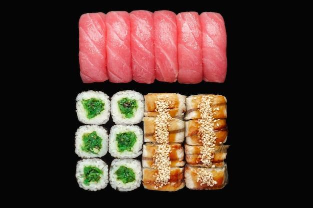 Sushi-rolle mit lachs, aal, japanischer mayonnaise, unagi-sauce, sesam, chuka, thunfisch-nigiri