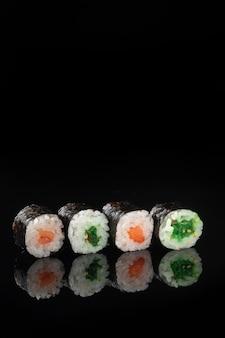 Sushi-rolle mit reflexion auf schwarzem hintergrund. ein restaurant mit japanischer küche. frauenhände halten sushi-rollen