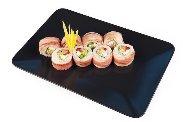 Sushi-rolle mit speck und gebratenem wolfsbarsch auf einem schwarzen teller