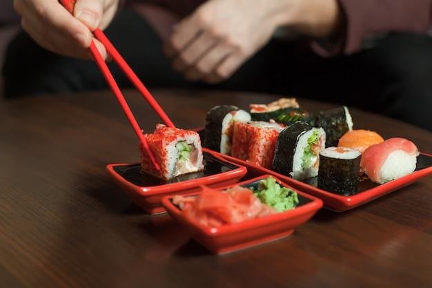 Sushi-rolle mit stäbchen halten.
