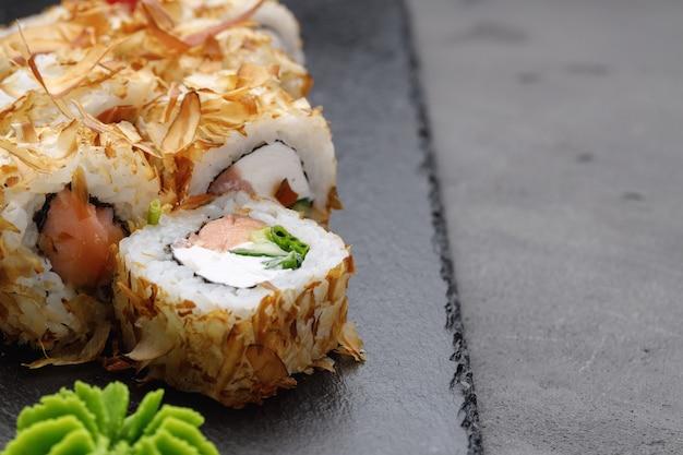 Sushi-rolle mit thunfischspänen auf teller nah oben