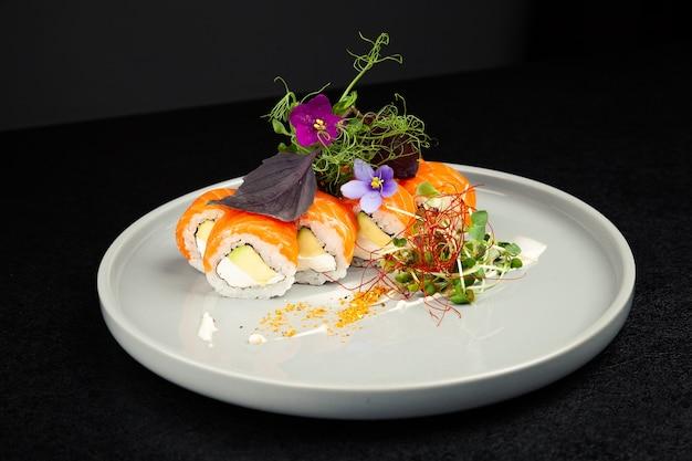 Sushi-rolle philadelphia mit avocado verziert mit kräutern auf einem teller, klassisches japanisches sushi. traditionelles japanisches essen mit maki.