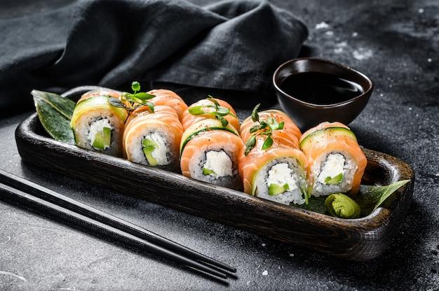 Sushi-rolle philadelphia mit lachs, avocado, frischkäse. sushi-menü. japanisches essen. draufsicht