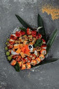 Sushi-rollen auf einem kristalltablett. brötchen: philadelphia, grüner drache, hawaii, roter drache, ebi shake.