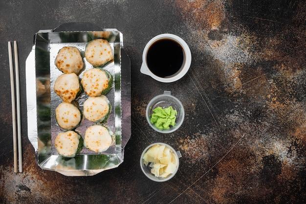 Sushi-rollen im imbissbehälter-satz, auf altem dunklem rustikalem