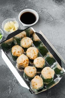 Sushi-rollen in behältern zum mitnehmen, philadelphia-rollen und gebackene garnelenrollen auf grauem steinhintergrund