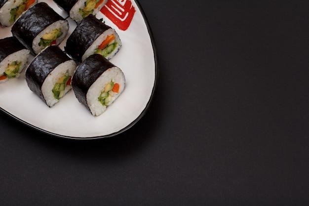 Sushi-rollen in nori-algenblättern mit avocado und rotem fisch auf keramikplatte. draufsicht mit schwarzem hintergrund und kopienraum.