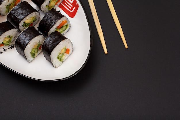Sushi-rollen in nori-algenblättern mit avocado und rotem fisch auf keramikplatte und holzstäbchen. ansicht von oben mit schwarzem hintergrund.