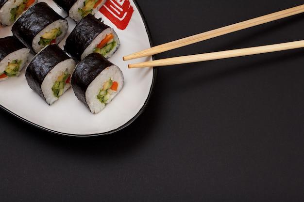 Sushi-rollen in nori-algenblättern mit avocado und rotem fisch auf keramikplatte und holzstäbchen. draufsicht mit schwarzem hintergrund und kopienraum.