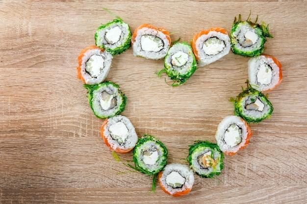 Sushi-rollen lagen in herzform auf dem tisch. feiertagssatz für valentinstag. ansicht von oben.