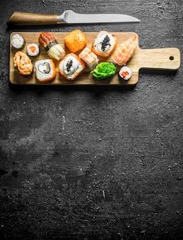 Sushi-rollen mit garnelen, gemüse und lachs auf einem schneidebrett mit einem messer. auf schwarzem rustikalem hintergrund
