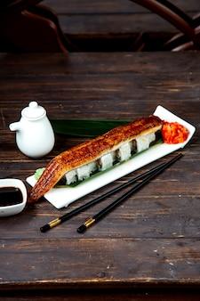 Sushi-rollen mit gebratenem fischfilet bedeckt