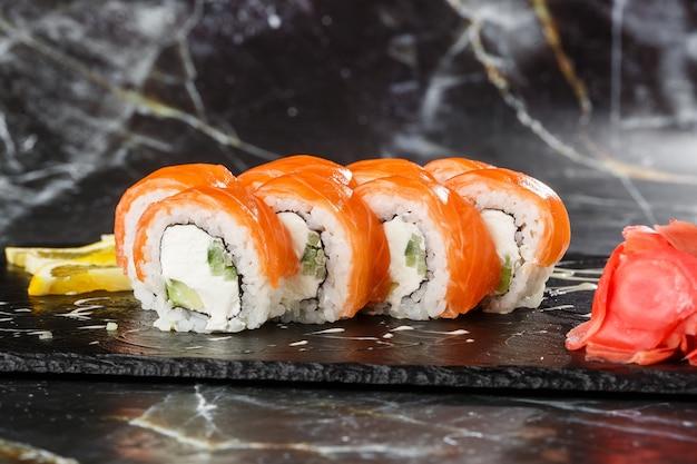 Sushi-rollen mit gurke, avocado, lachs und frischkäse innen auf schwarzem schiefer lokalisiert auf schwarzem marmorhintergrund. philadelphia roll sushi. sushi-menü. horizontales foto.