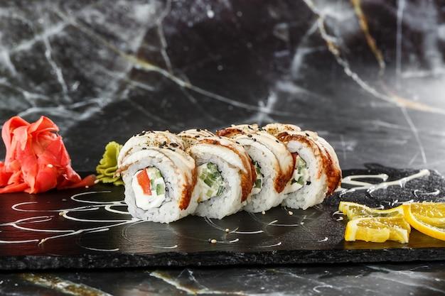 Sushi-rollen mit gurke, tomate, aal und frischkäse innen auf schwarzem schiefer lokalisiert auf schwarzem marmorhintergrund. philadelphia unagi roll. sushi-menü. horizontales foto.
