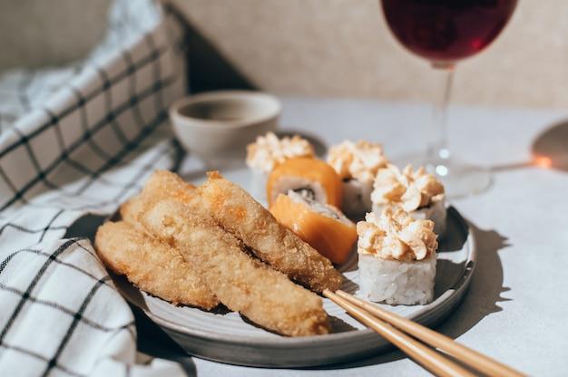 Sushi-rollen mit lachs, käsecreme und gebratenen garnelen auf grauem teller und glas rotwein