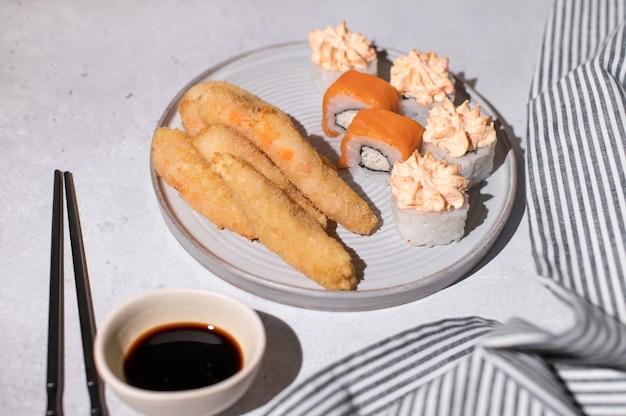 Sushi-rollen mit lachs, käsecreme und gebratenen garnelen auf grauem teller