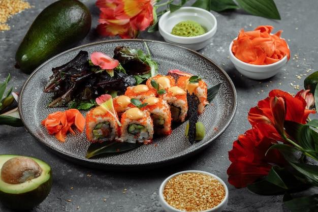 Sushi-rollen mit lachs, thunfisch, avocado, riesengarnele und frischkäse