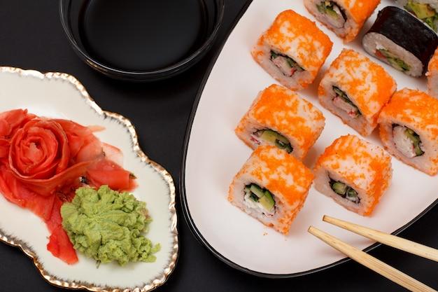 Sushi-rollen mit nori, reis, avocadostücken, gurken, flugfischrogen auf keramikplatte. teller mit rotem eingelegtem ingwer und wasabi. schüssel mit sojasauce. schwarzer hintergrund.