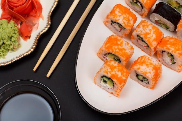 Sushi-rollen mit nori, reis, avocadostücken, gurken, flugfischrogen auf keramikplatte. teller mit rotem eingelegtem ingwer und wasabi. schüssel mit sojasauce und holzstäbchen. schwarzer hintergrund.