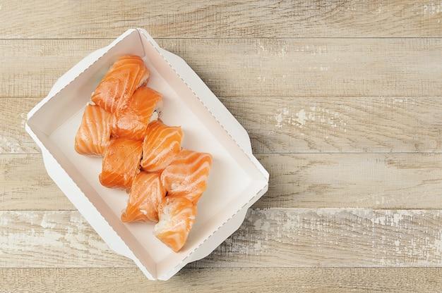 Sushi-rollen mit philadelphia-käse und lachs in einem karton