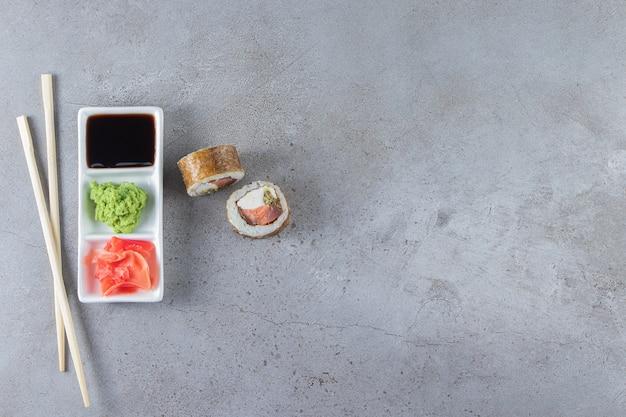 Sushi-rollen mit sojasauce auf ein weißes brett mit stäbchen gelegt.