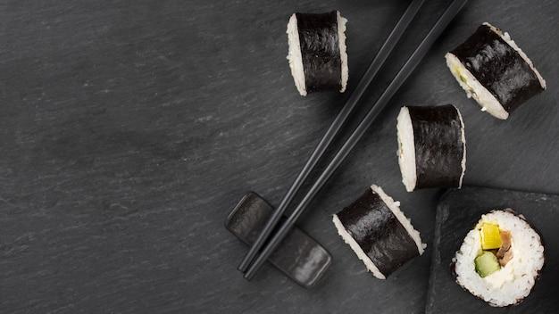 Sushi-rollen mit stäbchen und platz zum kopieren