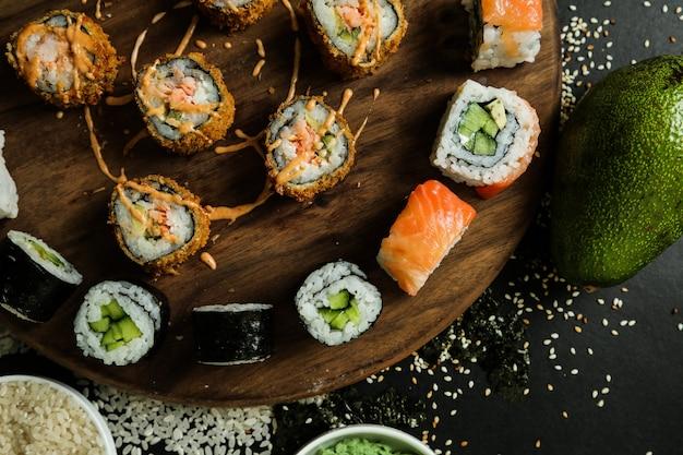 Sushi-rollen-set auf dem schreibtisch mit sauce draufsicht gekrönt