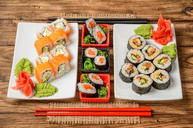Sushi-rollen-set mit verschiedenen fischen, gemüse, käse, sesam, ingwer und wasabi aus der nähe. holzstäbchen