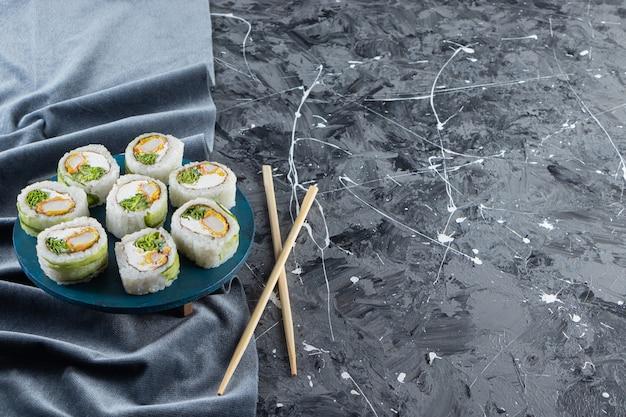 Sushi-rollen, sojasauce, wasabi und eingelegter ingwer auf steinhintergrund.